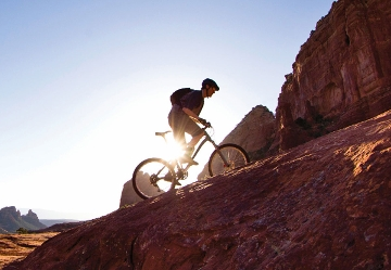 Silhouette of man riding up hill on mountain bike